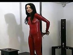 Tied brunette girl in red latex and high heels enjoys posing in front of the web camera